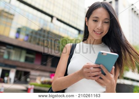 Young Woman working on smart phone in the city