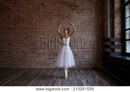 Indoor shot of graceful young European ballerina with athletic slender body standing on toes wearing white pointe shoes during traning routine in studio. Flexibility stamina and hardwork concept