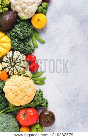 Above view of different colored rainbow vegetables on the light grey background, copy space for text, vertical, selective focus