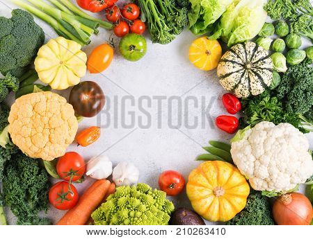 Colorful vegetables arranged in a circle on the light grey background, copy space for text in the middle, selective focus