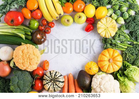 Assorted colorful vegetables and fruits arranged in a circle on the light grey background, copy space for text in the middle, selective focus