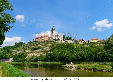 The historic Mělník castle and church tower of St. Peter and Paul at the confluence of the Vltava (Moldau) and Labe (Elbe) rivers on sunny early July afternoon in 2017.