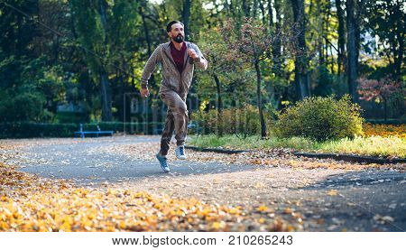 Healthy active man running in the park. Mid aged male jogging putdoors.