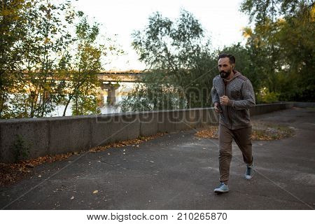 View of man running on river bank in the city. Jogging in nature, male enjoying music while running.