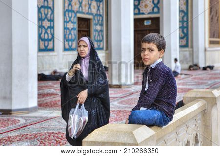 Fars Province Shiraz Iran - 19 april 2017: Shah Cheragh Shrine Muslim woman wearing an Islamic veil passes by one of the unknown boy about 10 years old.