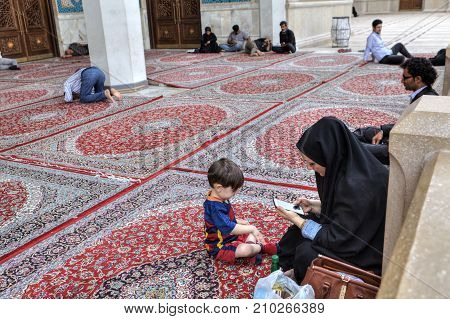 Shiraz Iran - 19 april 2017: Iranian Muslim woman dressed in a chador with her child a boy of five years old rests in the inner courtyard of the mosque near Islamic men rest and pray.