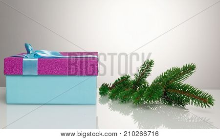 A beautiful gift box in blue, with a purple ribbon and bow. Next to it lies a branch of a Christmas tree. Beautiful christmas card on white background. An unusual postcard.