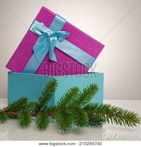 A beautiful gift box in blue, with a purple ribbon and bow. Before her is a green branch of a Christmas tree. Beautiful christmas card on white background. An unusual postcard.