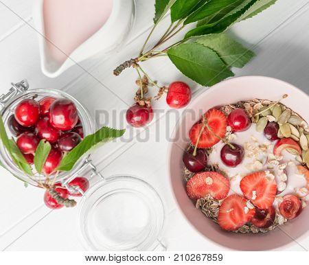 Healthy breakfast with muesli and cut cherries, rustic jar with yoghurt, topview