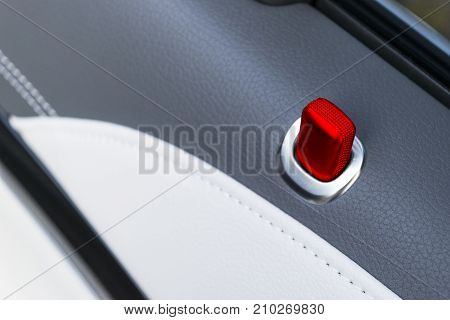 Door handle with red lock contol buttons of a luxury passenger car. Black leather interior of the luxury modern car. Modern car interior details