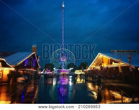 Stuttgart, Germany - October 5, 2017: Reflections of the beer tents and attractions of the Stuttgart Wasen Festival on a rainy evening.