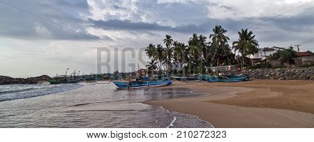 Sri Lankan traditional fishing catamarans Colorful fishing boats on a long sandy beach on the ocean coast of Sri Lanka. Popular landmark fishing Background Summer Landscape. Famous tourist attractions.