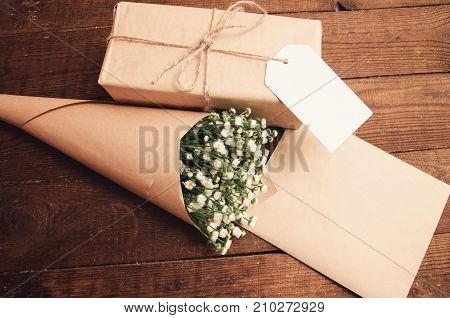 gift in package with bouquet of chamomiles wrapped in paper