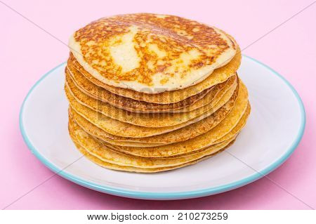 High stack of fried pancakes on pink background. Studio Photo