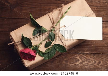 gift wrapped in kraft paper with rose flower on top