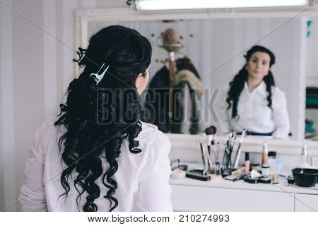 beauty salon girl with long black hair sits at the mirror in the beauty studio curly haired brunette expects a make-up artist in the hairdressing salon rear view
