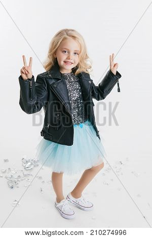 beautiful little girl with curly blonde hairstyle siting on the holiday party in dress with sequins and black jacket. Silver foil on the floor. Concept Celebration
