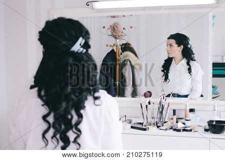 beauty salon girl with long black hair sits at the mirror in the beauty studio curly haired brunette expects a make-up artist in the hairdressing salon looking away