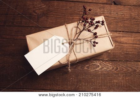 gift wrapped in kraft paper with a branch of dry berries at the top near the envelope