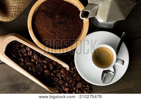 Coffee beans ground coffee powder and cup of espresso with stovetop coffee maker on dark wooden table background