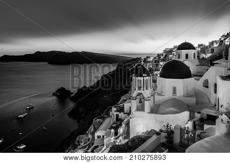 Black and white cityscape of Oia, traditional greek village with blue domes of churches, Santorini island, Greece at dusk.