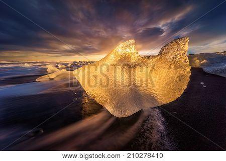 The iceberg in form of dolphin on Jokulsarlon black beach Iceland