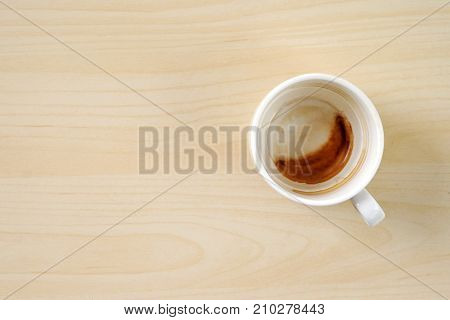 Coffee stain in cup on wood background with copy space