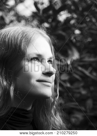 A young beautiful woman in the forest is looking ahead like watching something. A girl is squinting in the sunlight.