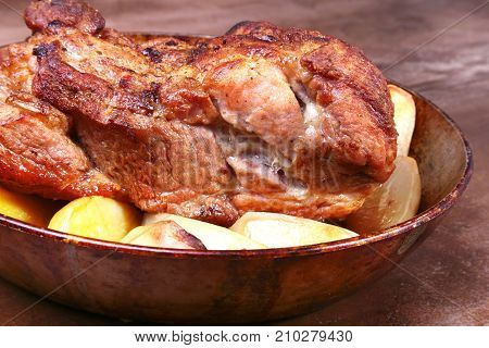 Juicy pork neck chops are grilled with potatoes on a stone Background