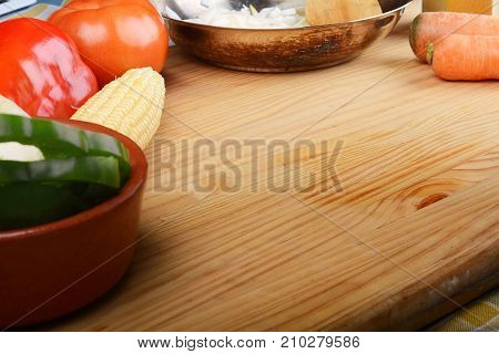 Vegetables and seasonings for cooking on wooden table.