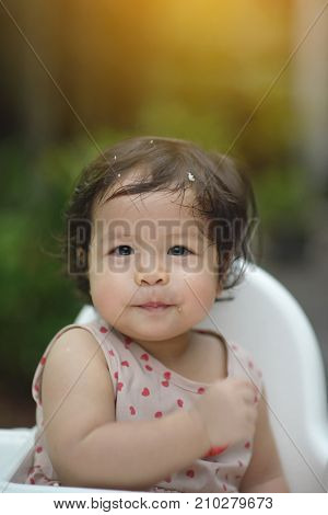 Portrait of a sweet Beautiful baby girl on a white eating chair Joyful Happy Excited Learning.