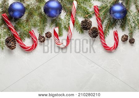 Christmas Or New Year Decoration Background: Fir-tree Branches, Blue Balls, Cones, Candy Under The S