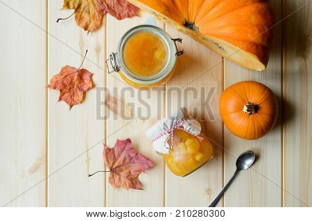 top view of autumn still life of organic pumpkin pumpkin jam in a jar maple leaves and spoon on natural wood table