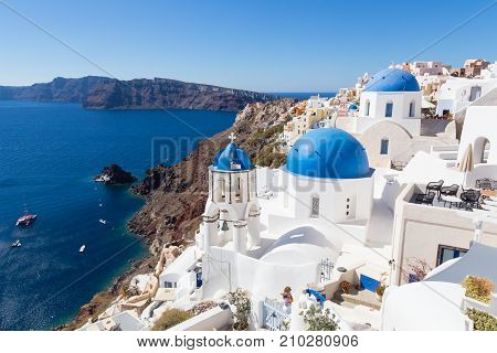 Cityscape of Oia, traditional greek village with blue domes of churches, Santorini island, Greece.