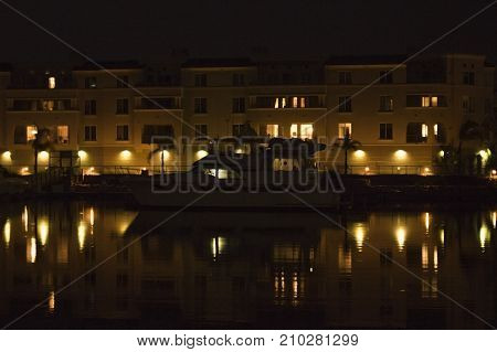 Boat in Front of Apartment Building in Dark Harbor with Reflection