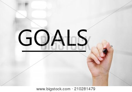 Hand holding pen and goals word on blur office background business concept