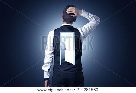 Young businessman standing and thinking with an open door on his back
