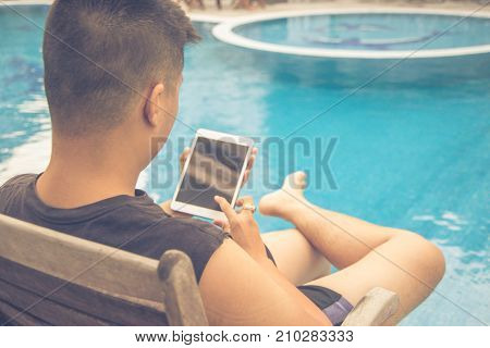 Young man urfing Internet on tablet and enjoy day at swimming pool
