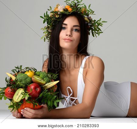 Beautiful woman with eatable bouquet of vegetables and fruits in pumpkin. Green leafs, kiwi peach lemon and figs