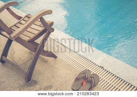 Wooden chair and orange slippers beside swimming pool