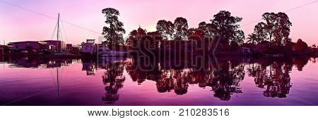 Colourful Magenta sunrise panorama over salt water something very special with clear water reflections and bold striking tree silhouettes. Photograph was taken on the Coomera River Gold coast Queensland Australia