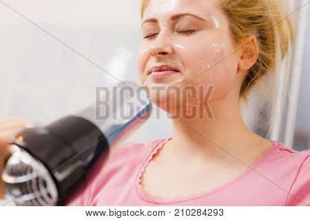 Woman Drying Her Peel Off Face Mask Hair Dryer