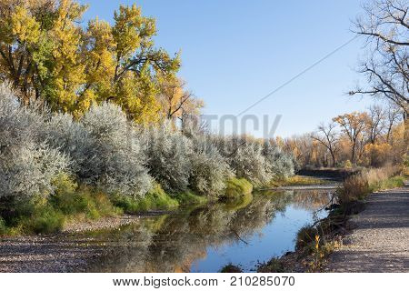 A shallow stream with bushes and trees on the bank. The reflection of the fall foliage is in the water. A trail follows the river's edge.