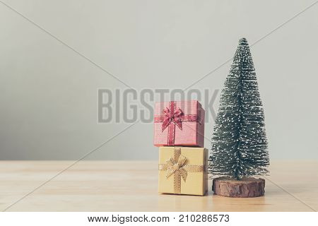 Christmas tree and gift box red yellow color on wood table with white wall background Christmas holiday celebration and boxing day concept Copy space