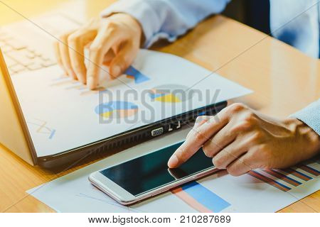 Businessman working with smart phone and laptop computer on wooden desk ; remote working concept; home business concept.