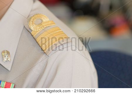 Thai teacher in formal officer government uniform with Brown suite and Golden stripe on shoulder thailand education