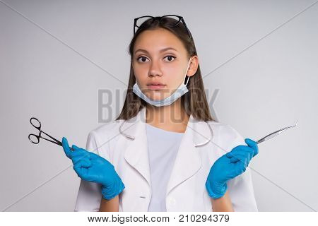 a girl in a medical uniform holds medical devices in her hands and cute will snort to the camera