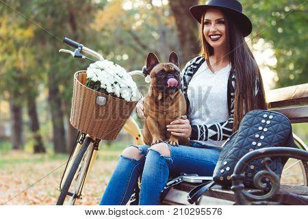 Girl with beautiful french bulldog, outside, sitting.