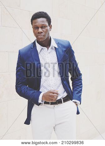 young man of african descent wearing smart casual men's fashion. faded color filter.