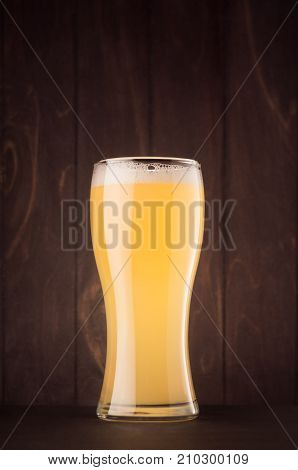 Beer glass with muddy weizen on dark wood board vertical. Template for advertising design branding identity restaurant menu cover.